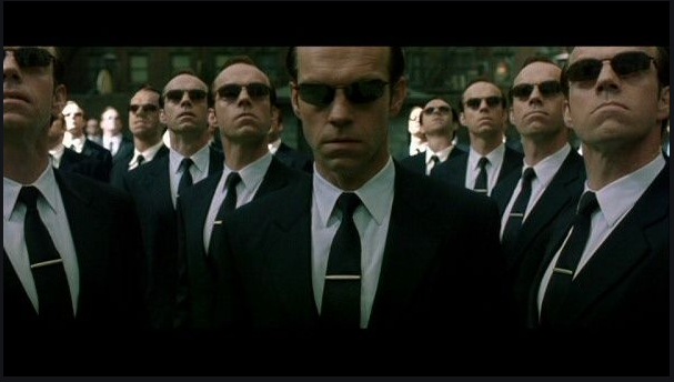 """Kadr z filmy """"The Matrix Reloaded"""". Na obrazie postać z filmu Agent Smith i stworzone przez niego klony. Postacie te mają symbolizować duplikaty w danych."""